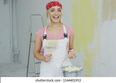 Young female in white overalls and red bandana on head standing with brush and bucket of yellow wall paint in hands smiling and looking at camera with stepladder and plastered wall on background.