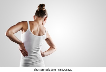 Young female in white shirt suffering from backache. Scoliosis treatment concept.