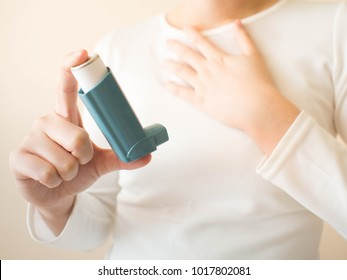 Young female in white t-shirt using blue asthma inhaler for relief asthma attack. Pharmaceutical products is used to prevent and treat wheezing and shortness of breath caused asthma or COPD. Close up.
