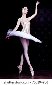 Young female / woman / girl ballerina in a white pack / tutu solo dancing and doing stand on toes in dark black scene with reflecting floor and dark background