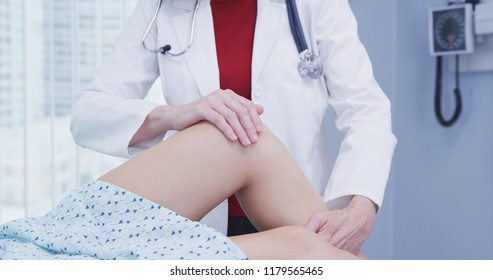 Young female woman having knee examined after sustaining injury in accident