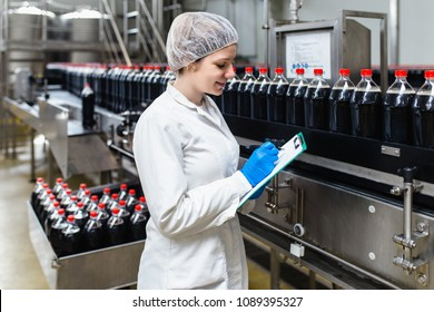 Young female worker in bottling factory checking juice bottles before shipment. Inspection quality control.