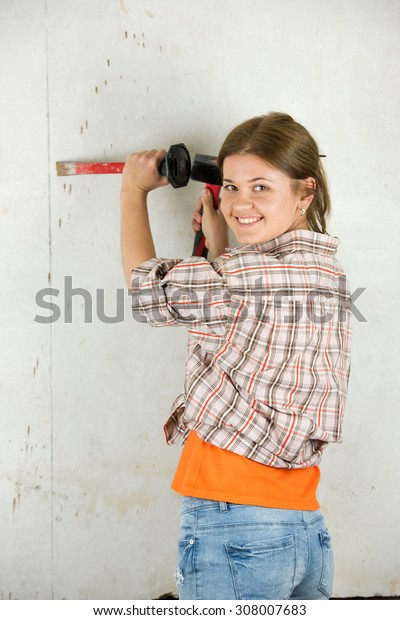 young female worker with  hammer and demolition tool repairing the wall