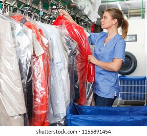 Young female worker of laundry inspecting clothing after dry cleaning on racks