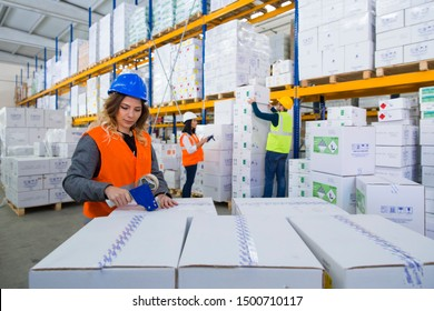 Young female worker packing boxes for shipment in warehouse