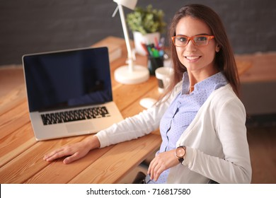 Young female working sitting at a desk.