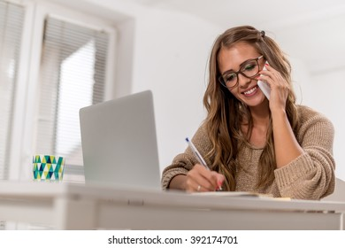 Young female writing notes while talking on phone