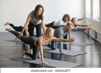 Young female yoga instructor teaching Bird dog pose, Knee to Forehead curl exercise for a group of sporty people practicing in studio, working out indoor, teacher helping to master, full length