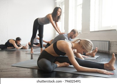 Young female yoga instructor teaching Janu Sirsasana pose, Head to Knee Forward Bend exercise for group of sporty people practicing in studio, working out, helping students to progress, full length