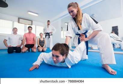 Young females are training in pair to use taekwondo technique during class.