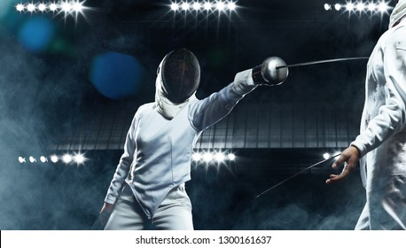 Young fencer athletes wearing mask and white fencing costume. Fight on the sword on black background with lights.