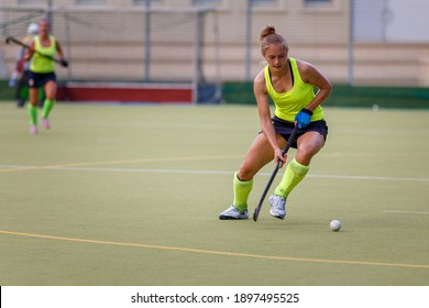 Young field hockey female player in attack. Sporty woman player leads the ball