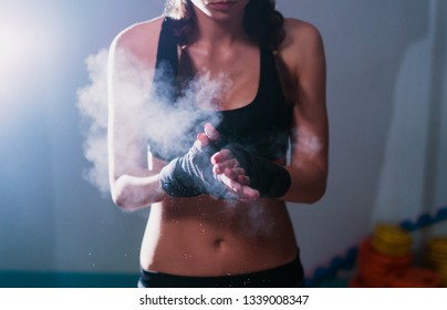 Young fighter boxer fit girl wearing hand bandage preparing before training. She has magnesia in hands