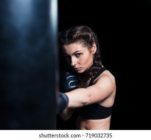 Young fighter boxer fit girl wearing boxing gloves in training with heavy punching bag in gym. Isolated on black background