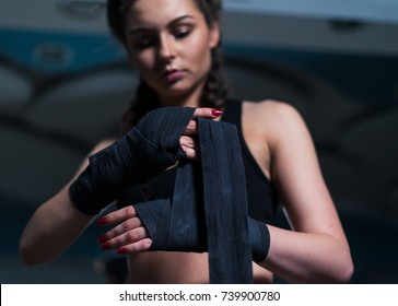 Young fighter boxer girl putting on hand bandage before training with heavy punching bag in gym. Low key image