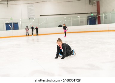 Young figure skater playing on indoor ice arena.