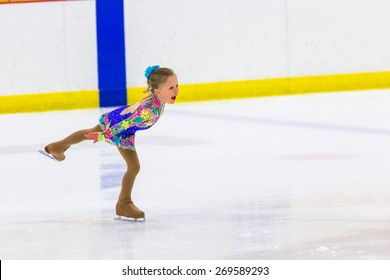 Young figure skater practicing at indoor skating rink.