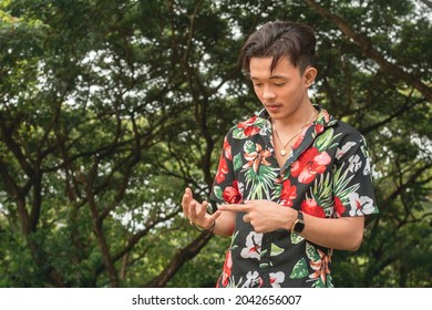 A young Filipino man in a hawaiian shirt counts with his fingers. Trying to list mentally his tasks for the day. Outdoor park scene.