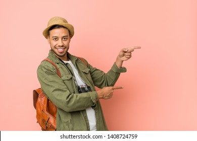Young filipino traveler man excited pointing with forefingers away.