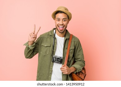 Young filipino traveler man showing victory sign and smiling broadly.