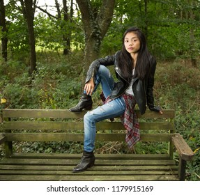 Young Filipino woman in black leather jacket in woods/forest setting sitting on old moss covered wooden bench in urban clothes. and jeans.