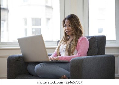 Young Filipino woman at home relaxing in her lounge and using a laptop