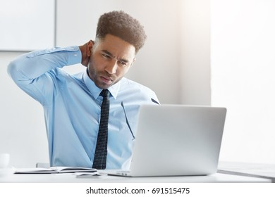 Young financial director working on his business report, looking with tired expression in his computer, keeping his hand on neck, having pain while sitting at his work place. Overwork concept.