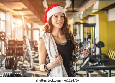 Young fir woman with red Santa hat, towel and water bottle in gym. New Year. Christmas, holidays, fitness, and gym concept.
