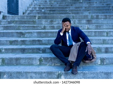 Young fired african american business man lost in depression crying sitting on ground street stairs suffering emotional pain sadness in grunge lighting. Unemployment, Depression and people concept.