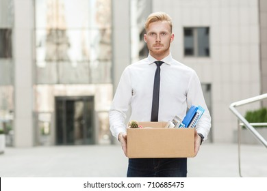 Young fired. Unhappy bearded business man going out with cardboard, looking at camera and feeling looser. Outdoor
