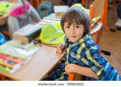 Young first grade student sitting at desk on his first day at school in the classroom