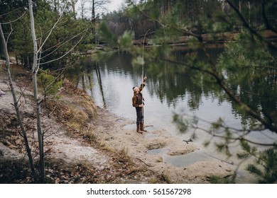 Young fisherman catches a fish on lake