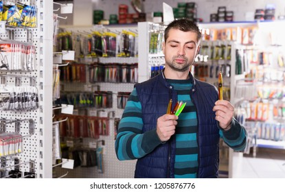 Young fisherman customer  buying new fishing lures in the fishing shop