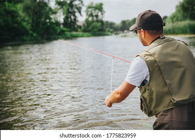 Young fisherman fishing on lake or river. Back view of guy looking at water and fishing alone. Holding rod in hands. Calm peaceful sumer nature. Sunshine and daylight.
