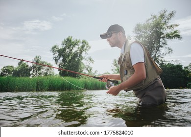 Young fisherman fishing on lake or river.Active guy in robe using rod for catching tasty delicious fish. Stand in deep water. Summer activity.