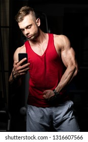 Young Fit Adult Man Taking A Selfie With Mobile Phone In Fitness Center - Gym In The Background