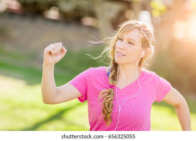 Young Fit Adult Woman Outdoors During Workout Listening To Music with Earphones.