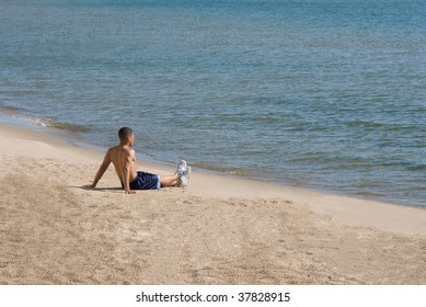 Young fit African American man relaxes on the beach