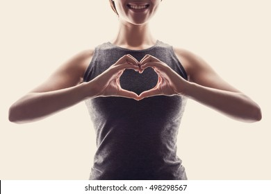 Young fit Asian woman make heart shape by her hands.