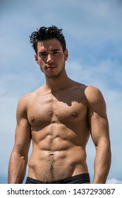Young fit athletic man at beach in summer day showing muscular torso, looking at camera