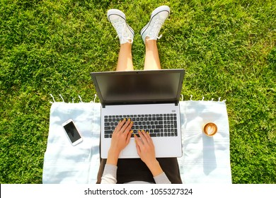 Young fit attractive woman sitting on green lawn park, working, browsing, surfing, blogging, eshopping on laptop computer. Coffee, cell phone gadget. Perks of freelance concept. Background, copy space