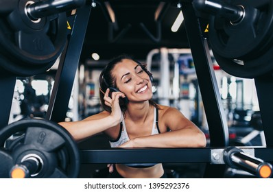 Young fit and attractive woman working out in modern gym and listening to music with bluetooth headphones and smart phone.