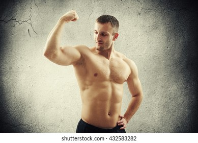 Young fit bare-chested man is showing biceps on his right arm isolated on old concrete wall background