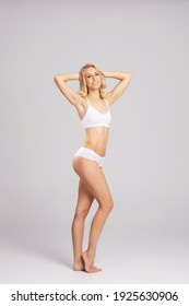 Young, fit and beautiful blond woman in white swimsuit isolated on grey. Healthcare, diet, sport and fitness concept.