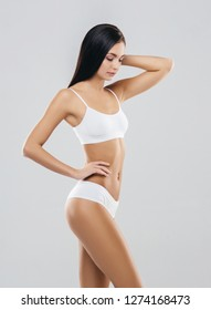 Young, fit and beautiful brunette girl in white swimsuit.