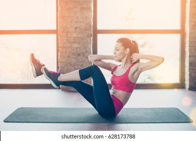 Young fit and beautiful sportswoman is exercising on the mat indoors. She is totally concentrated on her workout