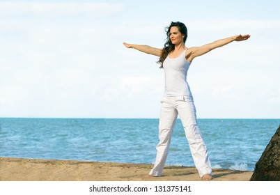 A young fit beautiful woman doing yoga on a beach with lots of copyspace.