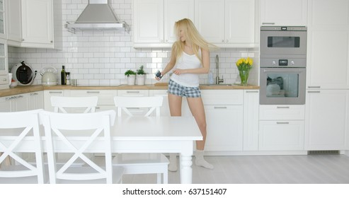 Young fit and beautiful woman wearing home clothing dancing in light kitchen alone and waving hair.