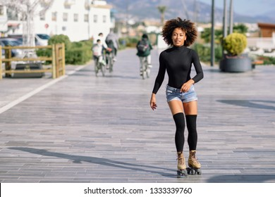 Young fit black woman on roller skates riding outdoors on urban street. Smiling girl with afro hairstyle rollerblading on sunny day. People ciclyng at background.