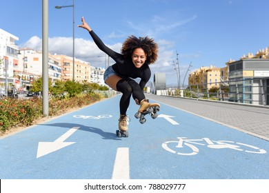 Young fit black woman on roller skates riding outdoors on bike line. Smiling girl with afro hairstyle rollerblading on sunny day